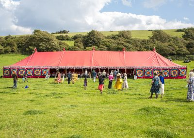 A colourful Mundir marquee provides the focus for a festival wedding on the South Downs in Sussex.
